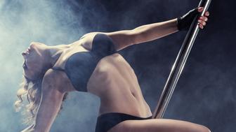 Sport. Pole dancer, woman dancing on pylon