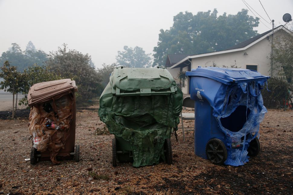 Melted garbage containers damaged by the wildfire sit near homes in Middletown, California, Sept. 13, 2015.&nb