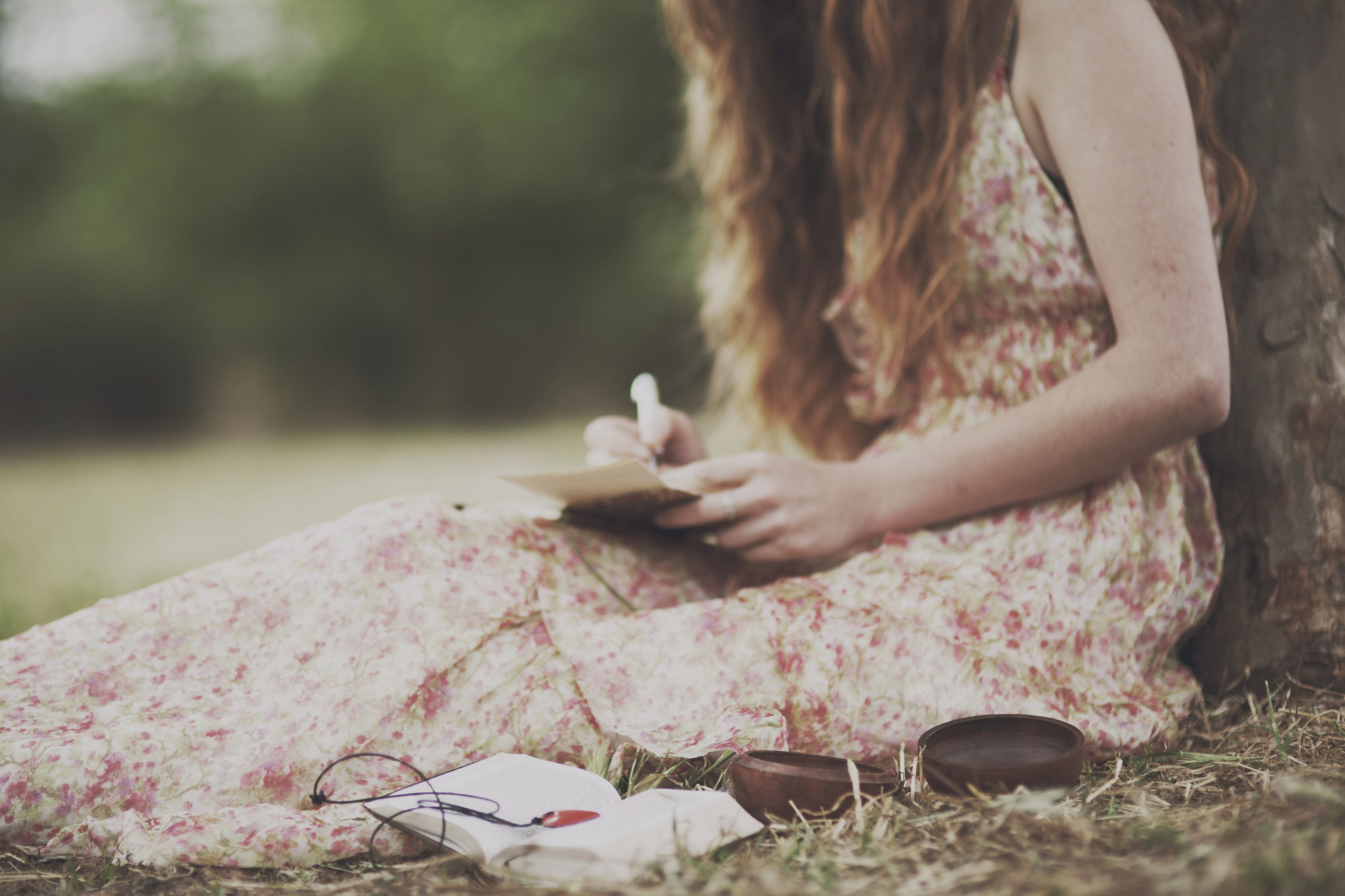 girl writes a letter under the tree