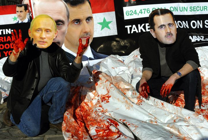 Activists wearing giant masks of Syrian president Bashar Assad and Russian president Vladimir Putin dump bloodied body b