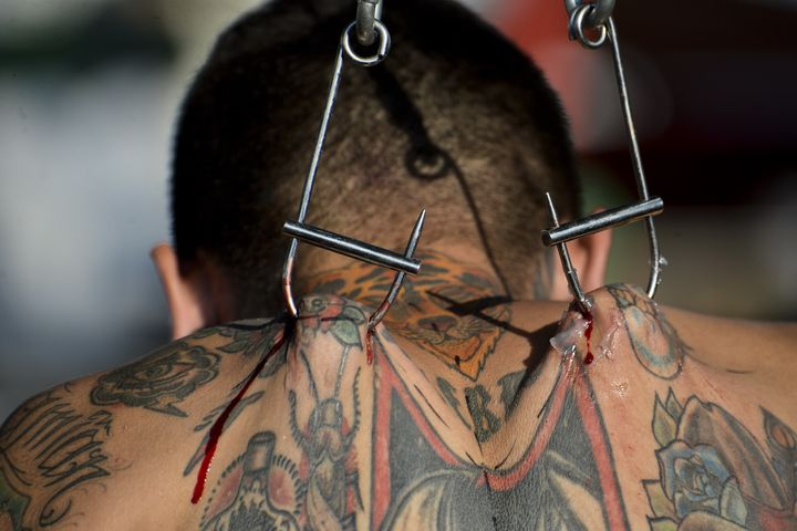 Body modification artist Damian Carnicero was suspended in the air with metal hooks attached to his back at the 2015 Cali Tat