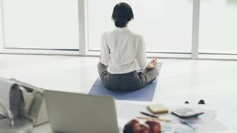 Office worker meditating on the floor, rear view