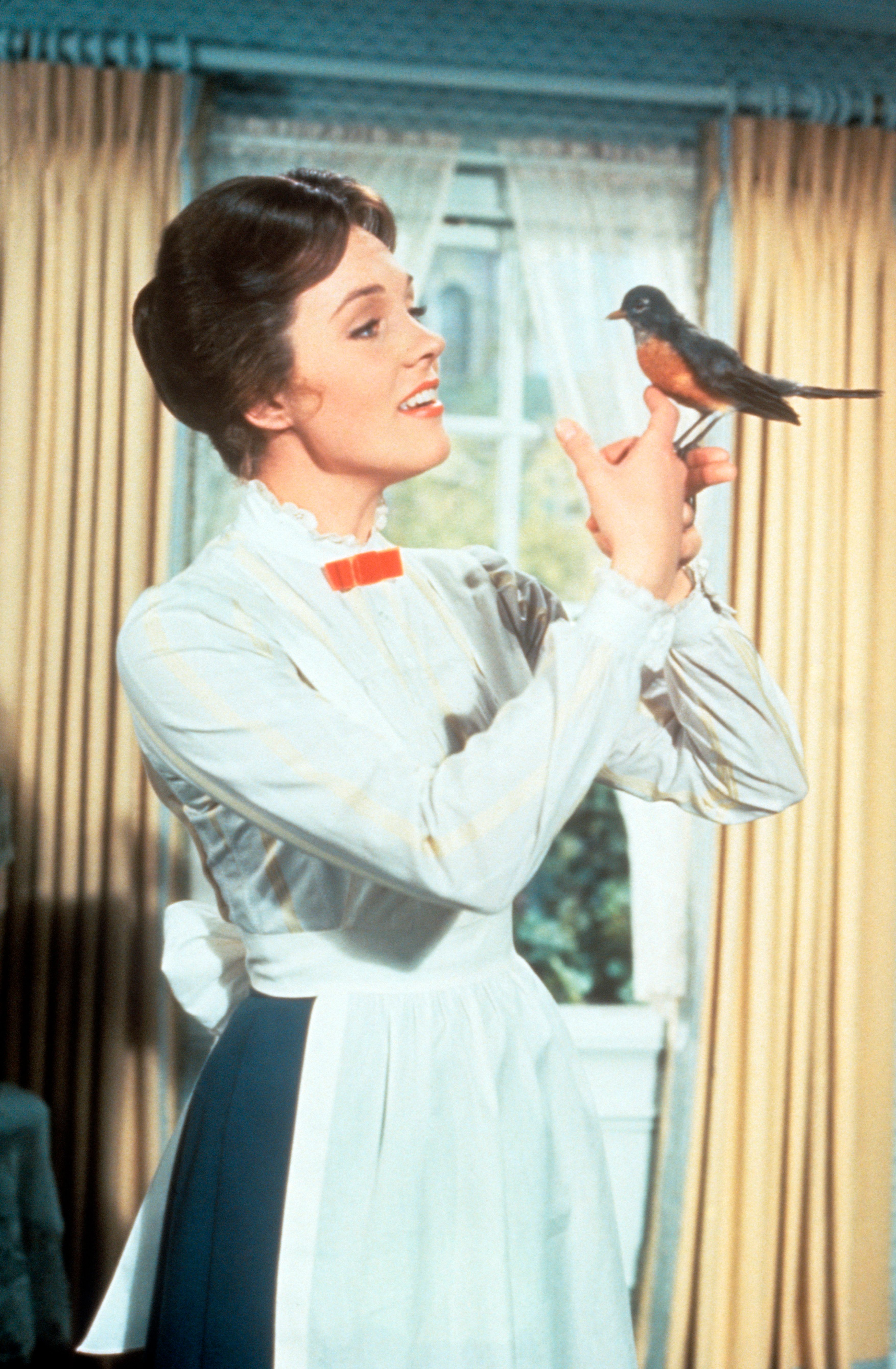 The British actress Julie Andrews, the pseudonym of Julia Elizabeth Wells, in the role of the nanny Mary Poppins, in the film of this name by Robert Stevenson, holds a robin in her hand in a scene of the film. USA, 1964.. (Photo by Mondadori Portfolio via Getty Images)