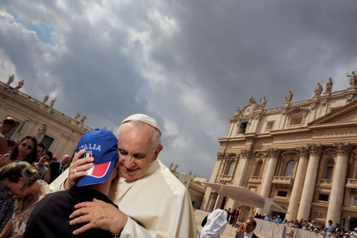 Pope Francis embraces a member of his flock during a Wednesday morning general audience. Tens of thousands of people, th