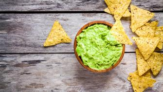 homemade guacamole with corn chips top view on rustic wooden table
