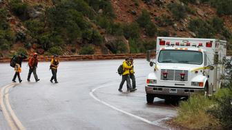 SPRINGDALE, UT - SEPTEMBER 15: Search and rescue personal finish their day of searching Pine Creek in Zion's National Park for lost hikers on September 15, 2015 in Springdale, Utah. Four hikers died and three are missing after a flash flood yesterday that also killed several woman and children in two vans that were swept away by the flood waters.  (Photo by George Frey/Getty Images)