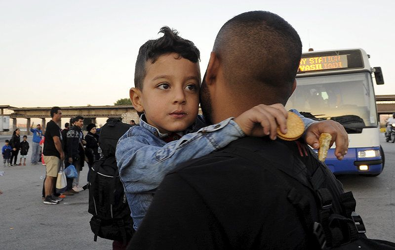 A Syrian refugee boy is carried toward a bus after disembarking a passenger ship at the port of Piraeus, near Athens, Greece,