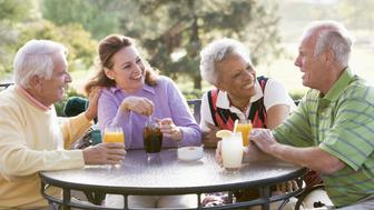 Friends Enjoying A Beverage By A Golf Course Sitting Down At Table Chatting