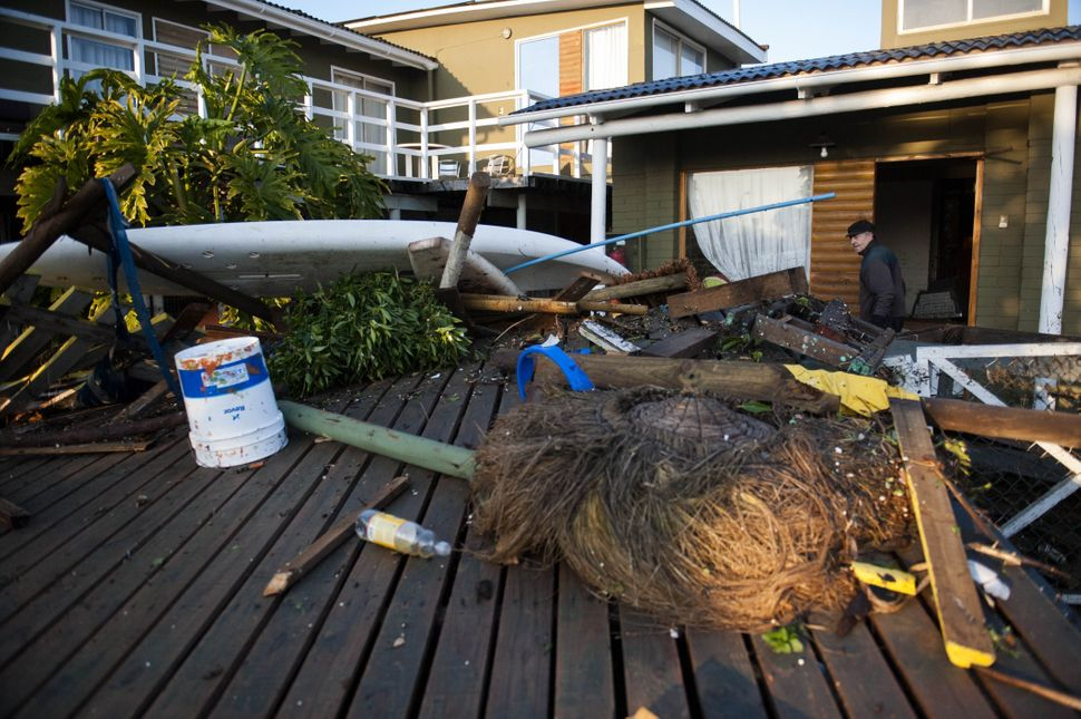 Fallen trees and other debris wash in front of houses in Concon, Chile, on Sept. 17, 2015.