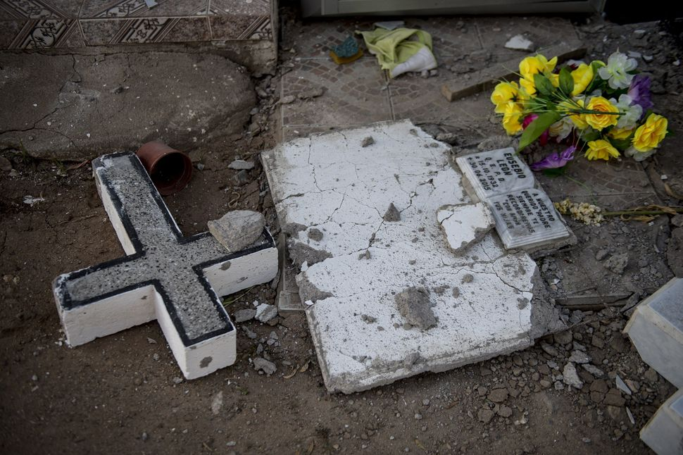 A headstone is damaged in a cemetery in Illapel, Chile, on Sept. 17, 2015.