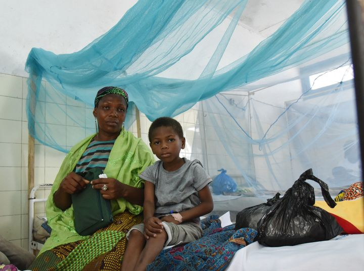 A mother sits with her sick child in a bed with mosquito net in a hospital on April 24, 2015 in the popular suburb of Port-Bo