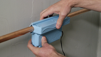 A user attaches the Fluid water meter onto a water pipe.