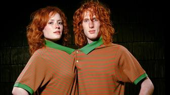 Redheaded man and woman in matching T-shirts connected buttons, portrait