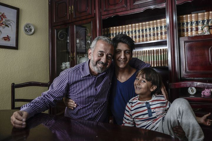 Osama Abdul Mohsen smiles with his 16-year-old son, Mohammed, and 7-year-old son, Zaid, at his apartment in Madrid, Spain, wh