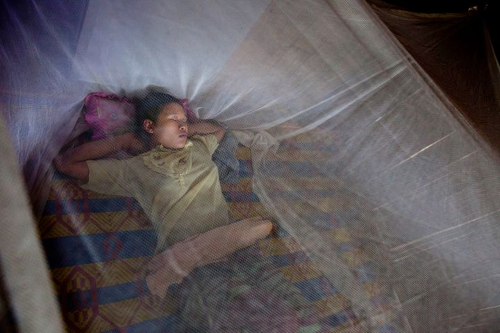 TAK, THAILAND - JUNE 6: A mother rests under a mosquito net as her newborn baby rests in a n incubator near by at the SMRU hospital maternity ward inside the Mae La refugee camp June 6, 2012 in Tak province, Thailand.
