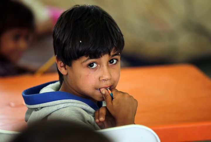 A Syrian refugee boy attends class at an unofficial refugee camp in the area of Arida, north of Beirut, on June 15, 2015. Rig