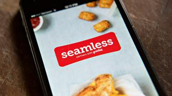 The Seamless app, acquired by rival GrubHub Inc. in August 2013, is displayed on an Apple Inc. iPhone 5 in Tiskilwa, Illinois, U.S., on Wednesday, April 2, 2014. GrubHub Inc., the Internet platform that enables users to order pick-up and delivery from restaurants, raised the expected price range for its initial public offering to $23 to $25 per share from $20 to $22 in a regulatory filing on Tuesday. The company plans to list on the New York Stock Exchange under the ticker symbol GRUB. Photographer:  Daniel Acker/Bloomberg via Getty Images