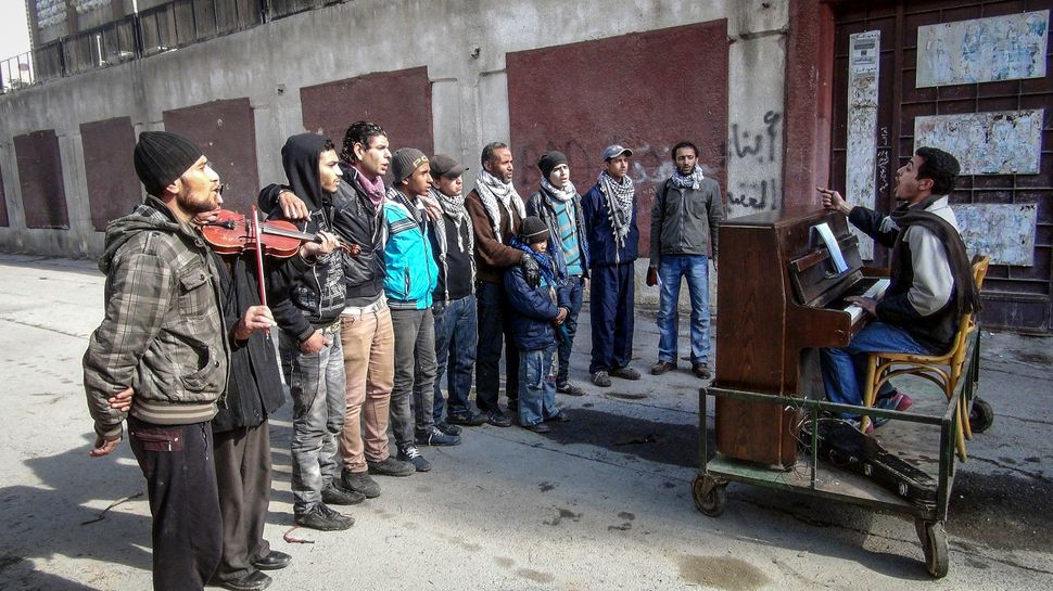 Ayham Ahmed plays the piano for his troupe of singers on the streets of Yarmouk, Syria, on Feb. 6, 2014.