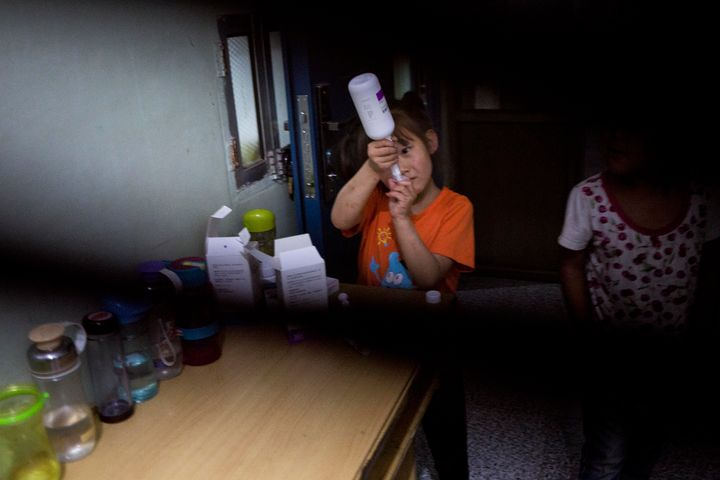 A third-grader takes her daily medication for HIV at Green Harbor.