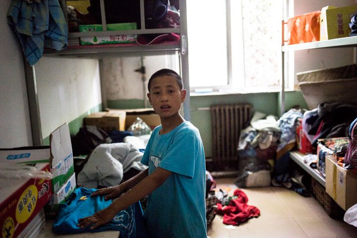 Jingtao, 14, tries to find clothes for his trip to Beijing in the storage room.