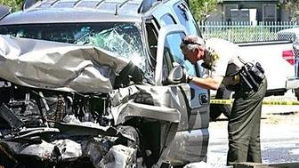 A deputy checks an SUV involved in a crash on Interstate 215 at the Little League Drive freeway overpass in San Bernardino, Calif., Friday, Sept. 18, 2015. Authorities say a wrong-way freeway driver has died in California after being shot at from a San Bernardino County sheriff's helicopter during a chase.