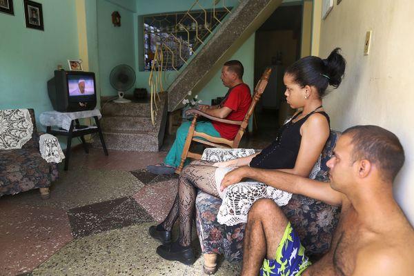 SANTIAGO DE CUBA, CUBA - SEPTEMBER 19:  People watch as Pope Francis is shown on television as he arrives in Havana, Cuba on