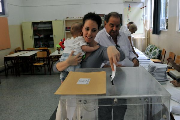 A woman holds her baby in her arms as she casts her ballot at a polling station in Thessaloniki.