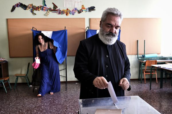 An Orthodox priest casts his vote at a polling station in central Athens.