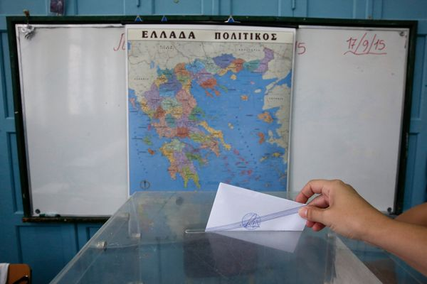 A voter casts her vote in a ballot box in front of a map of Greece in a polling station in the suburb of Marousi, Athens.
