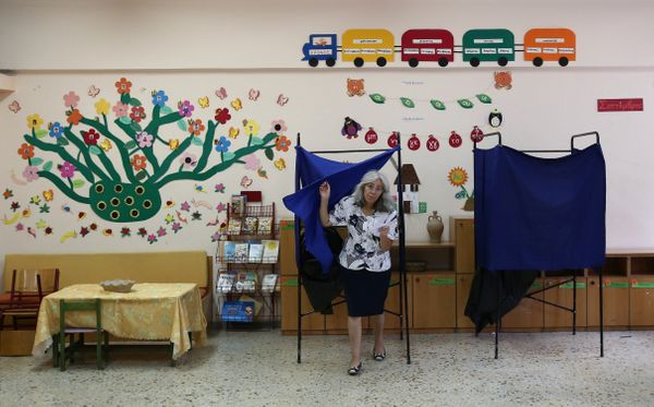 A Greek woman casts her ballot in the general elections at a polling station in Athens.