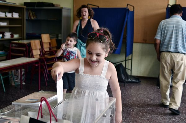 A girl casts her mother's vote at a polling station in central Athens.