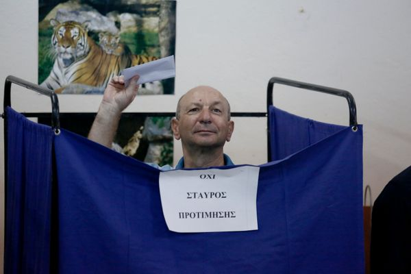 A voter holds his ballot slip above the curtain of a polling booth in the suburb of Kypseli, Athens.