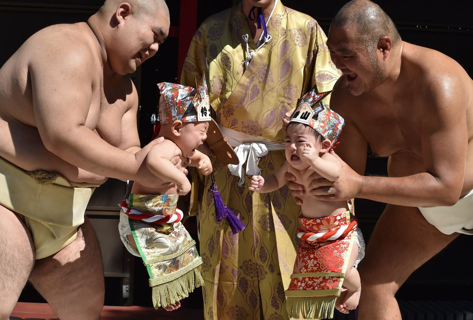 Sumo wrestlers hold up crying babies during a 'Baby-cry Sumo' event at the Irugi Shrine in Tokyo on Sept. 20, 2015. Japanese