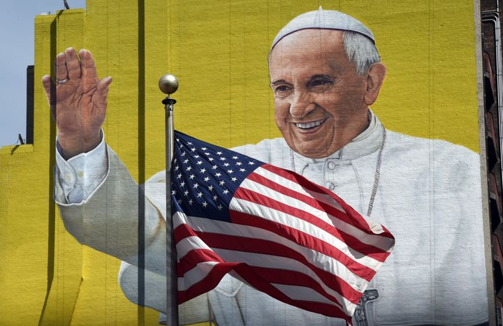 A US flag blows in the wind in front of a mural of Pope Francis across the street from Madison Square Garden in New York Sept