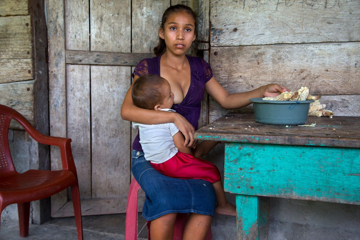 """Aracely, 15, of Guatemala holds her infant. """"What I hope is to keep moving forward ... to see how I can get my boy ahead. The"""