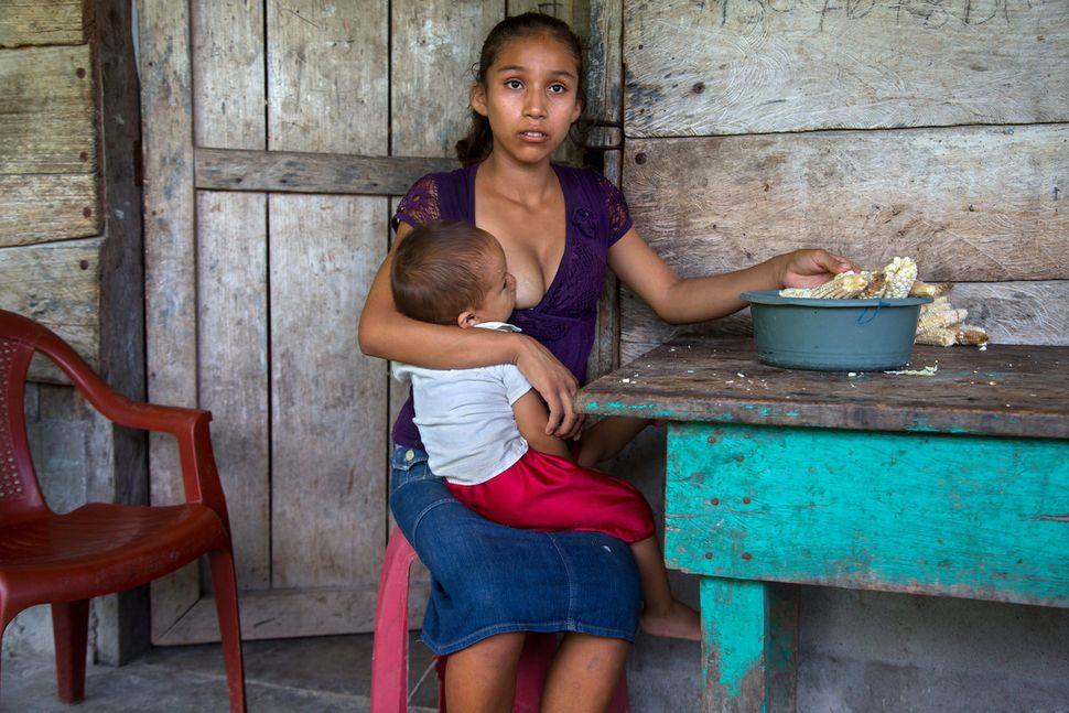 "Aracely, 15, of Guatemala holds her infant. ""What I hope is to keep moving forward ... to see how I can get my boy ahead. The"