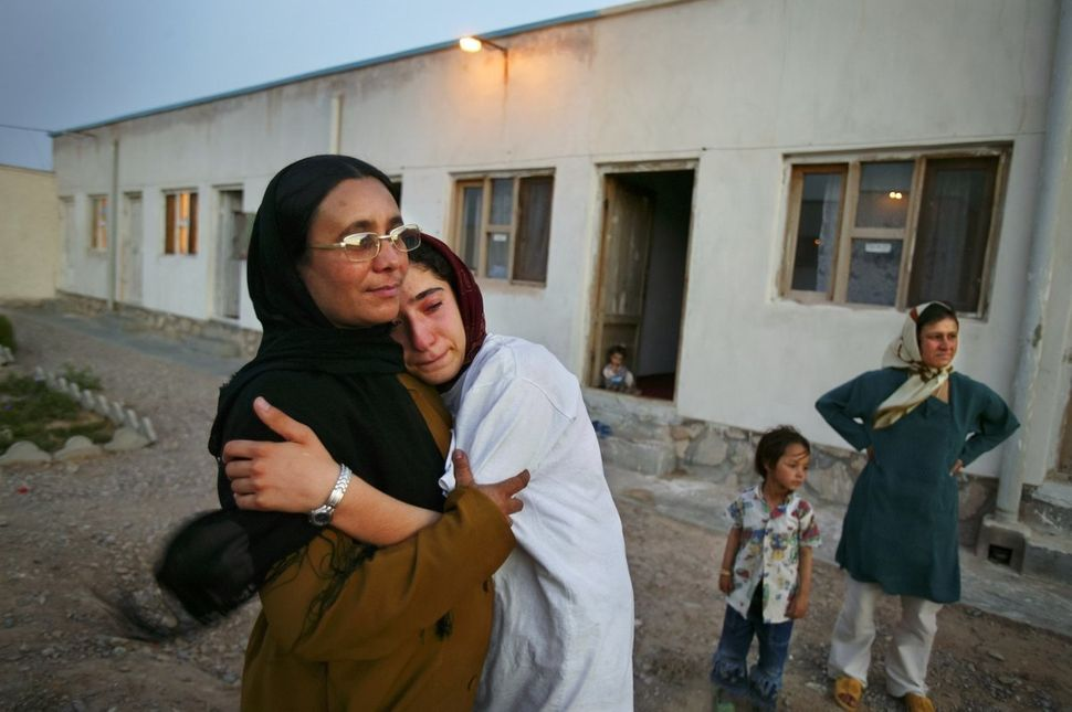 Mejgon, 16, weeps in the arms of her caseworker near fellow residents at an NGO shelter run by Afghan women in Herat, Afghani