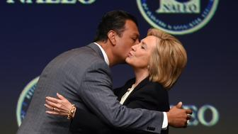 California Secretary of State Alex Padilla (L) greets Democratic presidential candidate and former U.S. Secretary of State Hillary Clinton. Both support automatic registration.