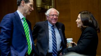 Senator Ron Wyden, a Democrat from Oregon, from left, Senator Bernard 'Bernie' Sanders, an independent from Vermont, and Senator Maria Cantwell, a Democrat from Washington, talk before a Senate Energy and Natural Resources Committee business meeting to markup an original bill to approve the Keystone XL pipeline in Washington, D.C., U.S., on Thursday, Jan. 8, 2015. Senate Majority Leader Mitch McConnell has vowed to make Keystone the first bill passed in 2015. House Speaker John Boehner also plans to push a bill. Photographer: Andrew Harrer/Bloomberg via Getty Images
