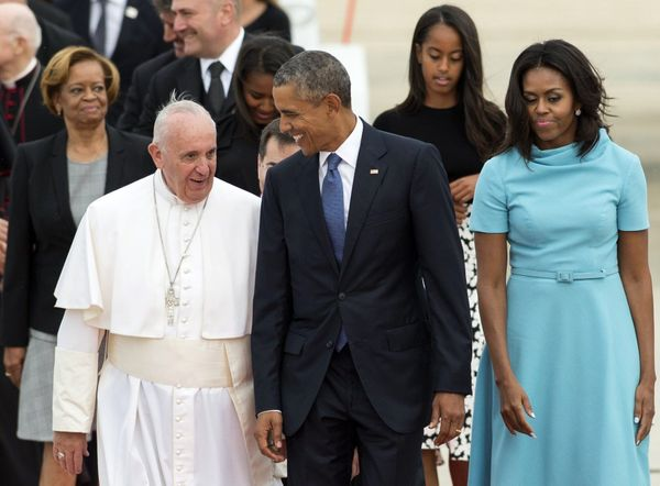 Pope Francis (L) walks alongside US President Barack Obama (C) and US First Lady Michelle Obama (R) upon arrival at Andrews A