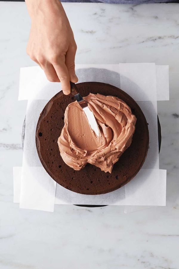 Line the edges of a cake stand or plate with strips of parchment. Place one cake layer on stand, trimmed-side up, and spread