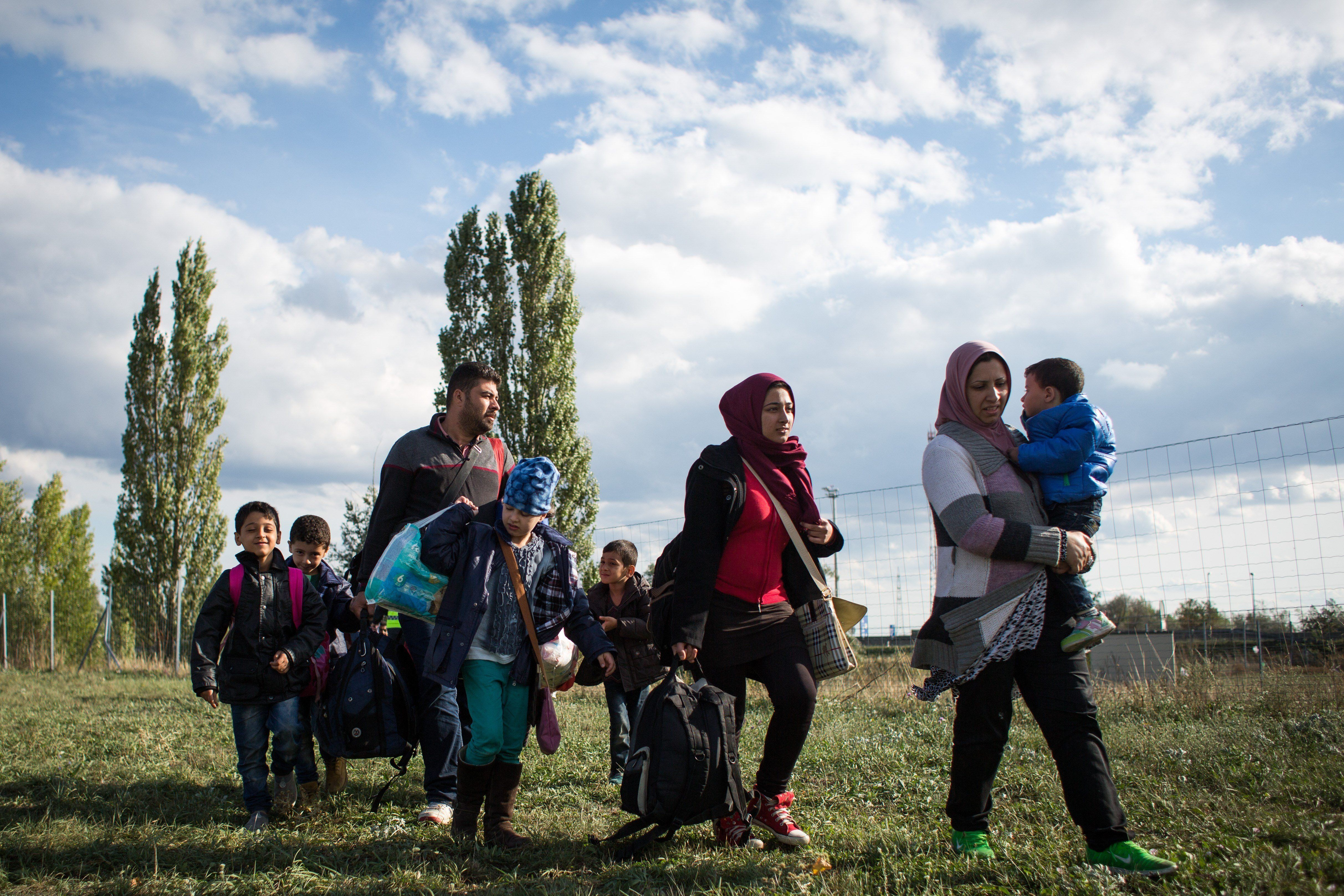 A refugee family from Iraq walks further in to Austria in Nickelsdorf at the Austrian-Hungarian border on September 20, 2015. Crowded aboard buses and trains, thousands more migrants flooded into Austria from countries unable or unwilling to cope with a desperate human tide fleeing war and poverty for a better life in western Europe. AFP PHOTO / VLADIMIR SIMICEK        (Photo credit should read Vladimir Simicek/AFP/Getty Images)