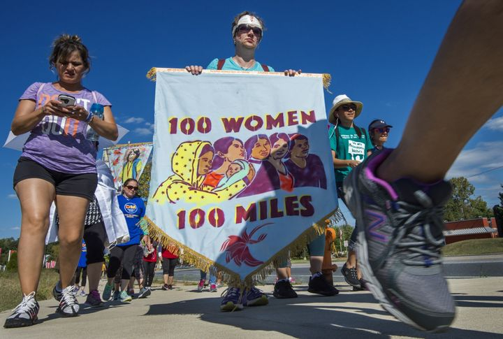 "Participants in the ""100 Women 100 Miles Pilgrimage"" walk on a road after a lunch break on their trek, after stopping at the"