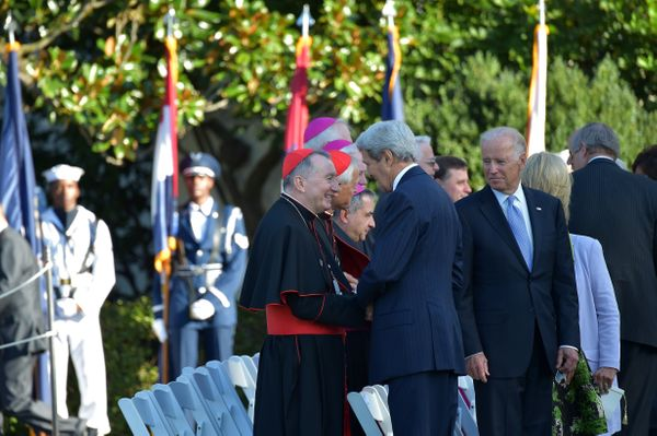 US Secretary of State (C) greets clergy  as US Vice President Joe Biden (R)  looks on before the arrival of Pope Francis at t