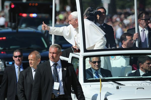 WASHINGTON, DC - SEPTEMBER 23: Pope Francis leans out and waves to the crowd as he rides in a popemobile along a parade route