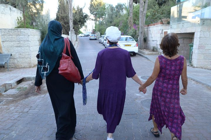 Three women, including Elana Rozenman, Abrahamic Reunion co-founder and founder of TRUST-Emun, center, hold hands during the