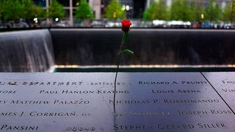 A rose is placed on a name engraved along the South reflecting pool at the Ground Zero memorial site during the dedication ceremony of the National September 11 Memorial Museum in New York on May 15, 2014.