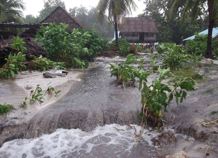 Flood water gushes through the island nation of Kiribati following a storm in March 14. The island nation faces extinction as