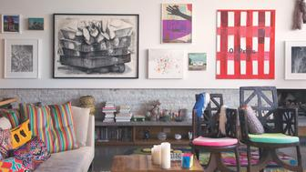 """<strong>The home of Cindy Sherman:</strong>An installation in Sherman's living room consists of, from top left, a work by John Hiltunen next to a small painting by Esther Pearl Watson, with James Welling's 2010 photograph below. To the right, a large black-and-white drawing of a buried man by Dana Schutz, """"(Untitled) Dead Guy,"""" from 2003; Michele Abeles's print of an outstretched hand; and an exploding thread piece by Megan Whitmarsh. Another small Watson lives beside Martin Kippenberger's 1944 """"O'Preis"""" painting. On the far right, the 1990 fabric piece """"Double Flaccid Cat"""" by Mike Kelley sits above a second Welling photograph. On the top shelf are Chris Garofalo's ceramics, and on the left a piece by Ken Tisa."""