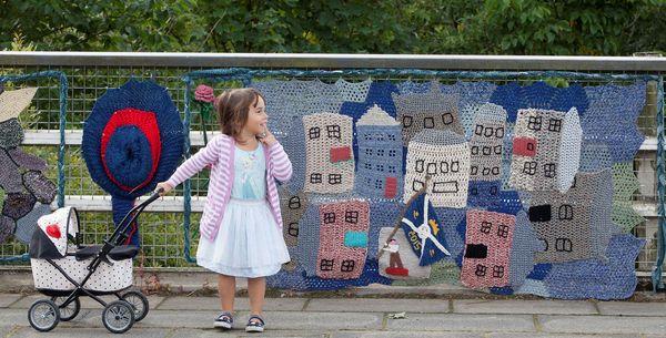 Three-year-old Faye Pearse alongside knitted art in Selkirk, Scotland.